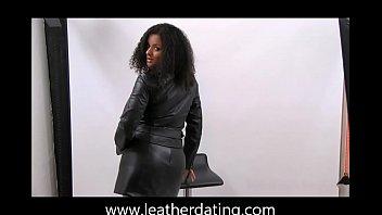 dark-hued bombshell posing in leather jacket miniskirt top.